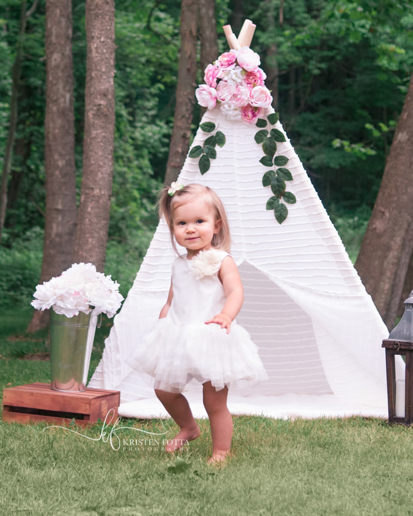 outdoor styled photos session for little girl with lacy tent and fresh flowers