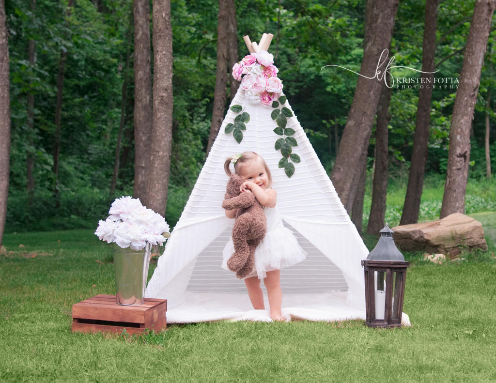 toddler girl hugging teddy bear during styled outdoor photo session with lacy tent and fresh flowers