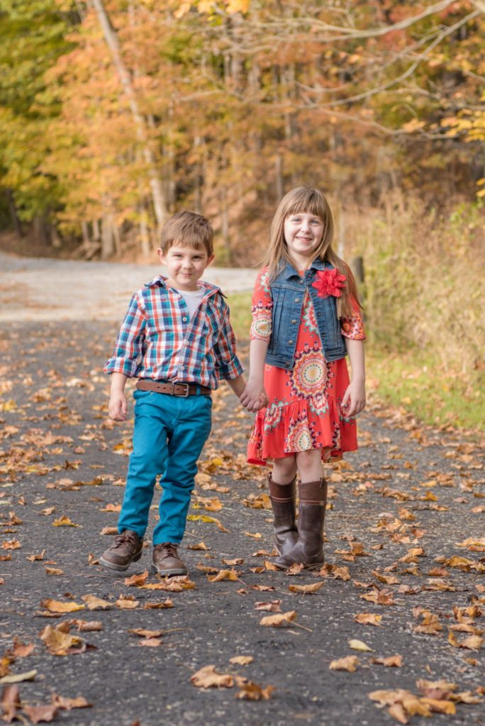 picture of brother and sister holding hand walking through fall leaves