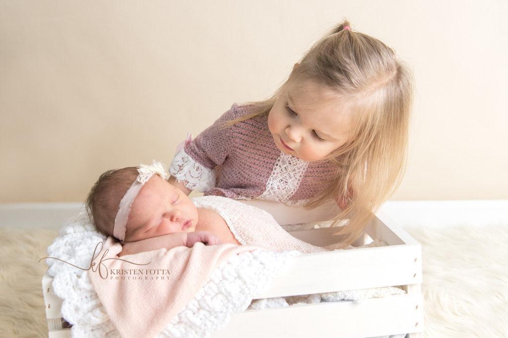 big sister looking at newborn baby sister
