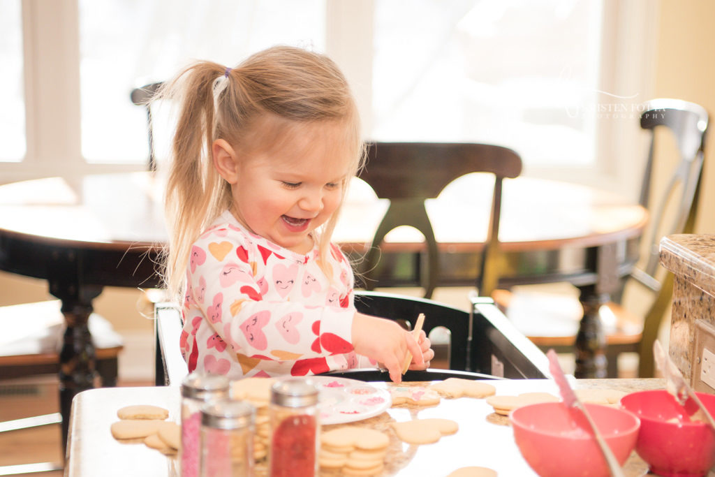 toddler girl laughing as she sprinkles Valentine cookies