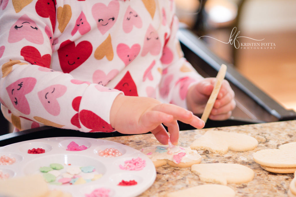 close up of girl decorating Valentine's Day Cookies