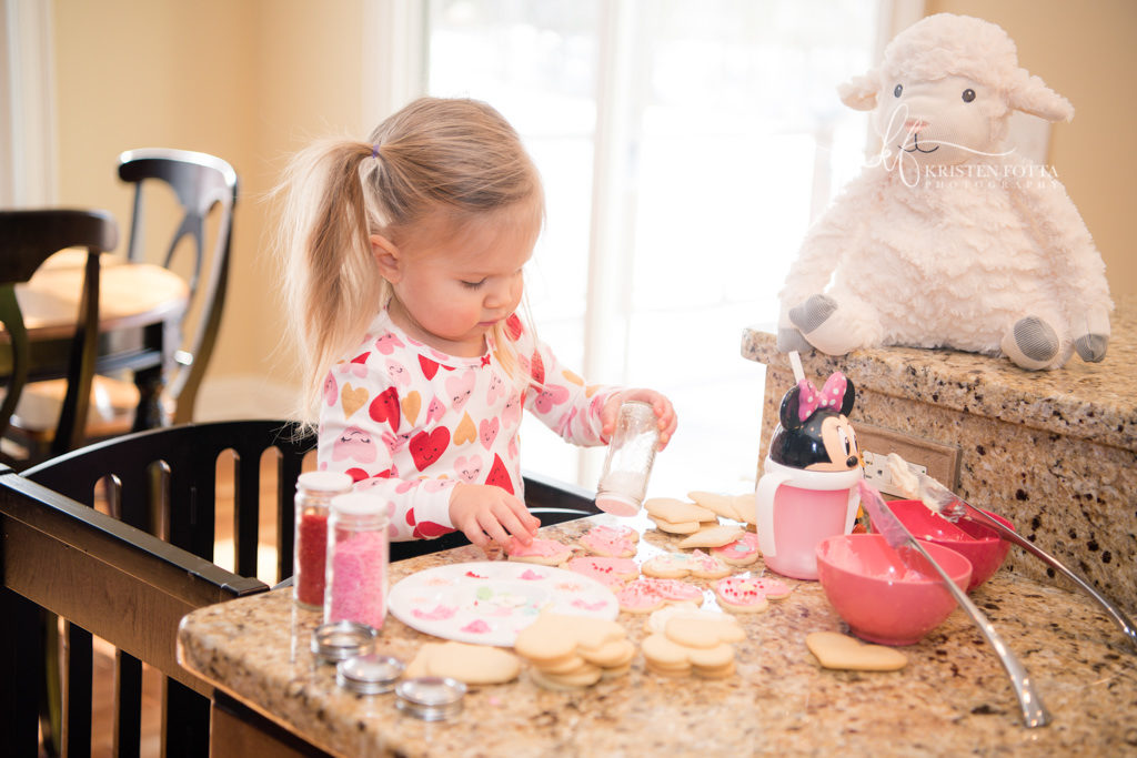 little girl in Valentine jammies decorating heart shaped cookies