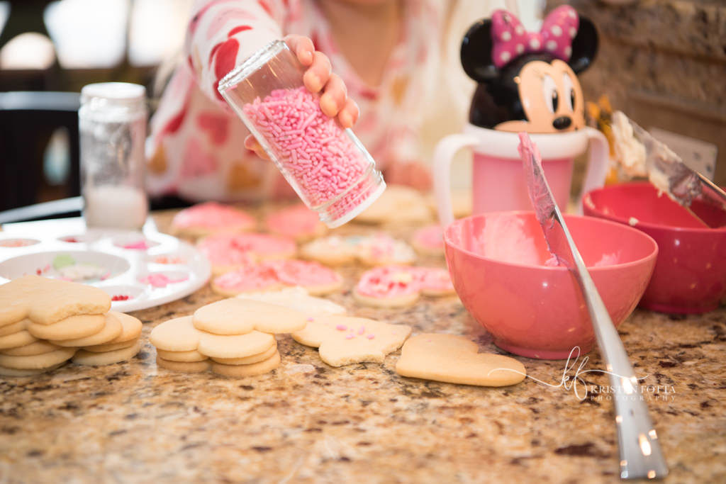 toddler girl decorating Valentine cookies with sprinkles
