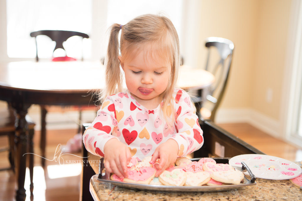 toddler girl in valentine pjs decorating heart shaped cookies
