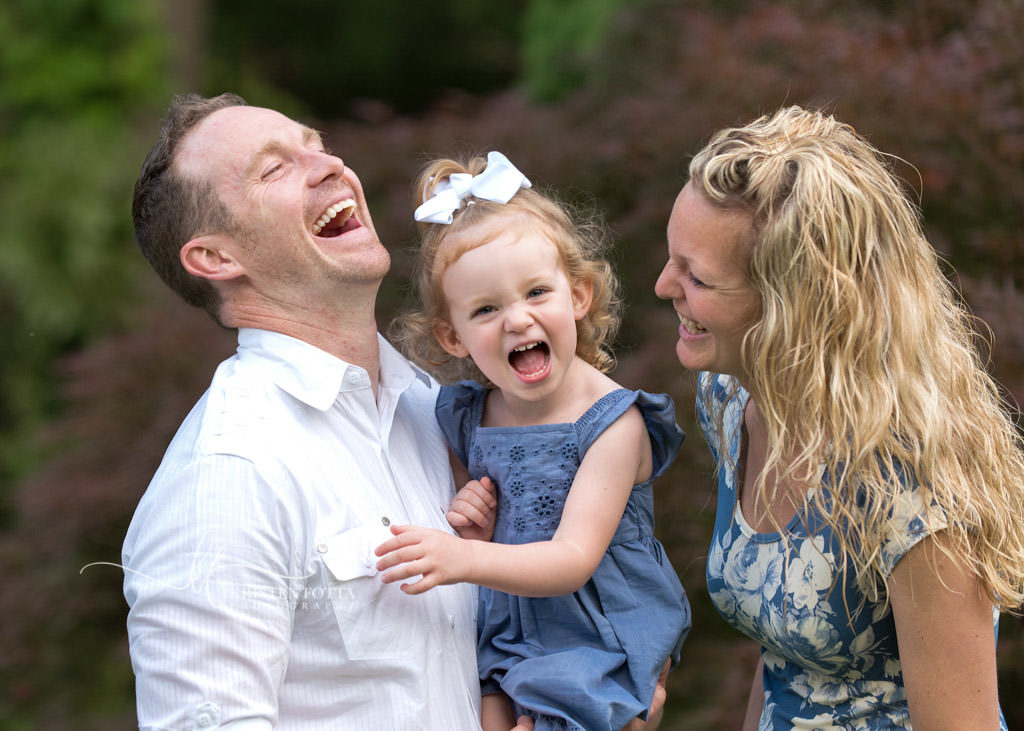family and toddler girl laughing together