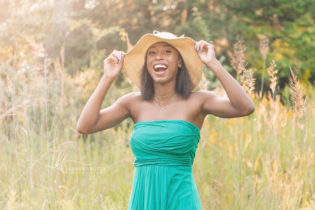 senior girl holding straw hat and laughing