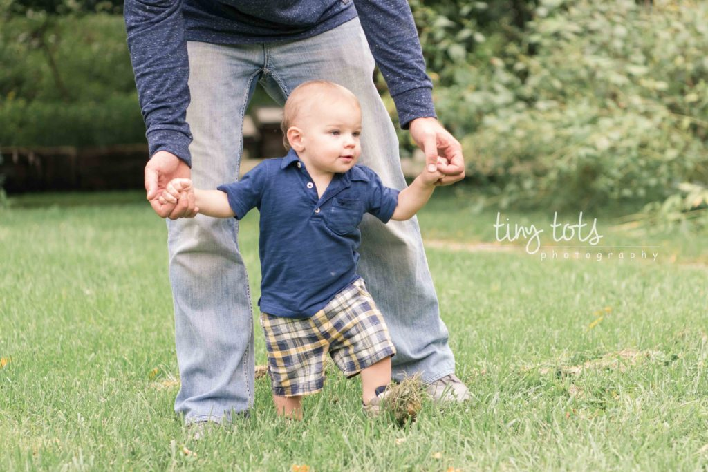 baby boy walking holding dad's hands