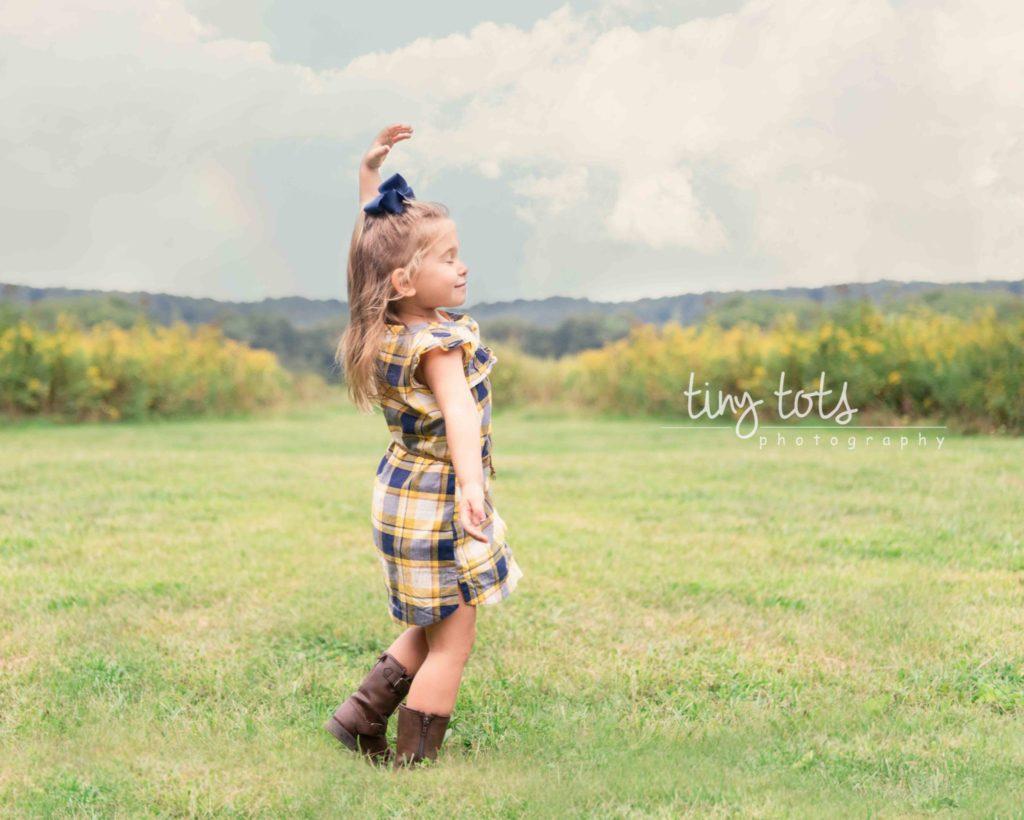 little girl dancing in a field