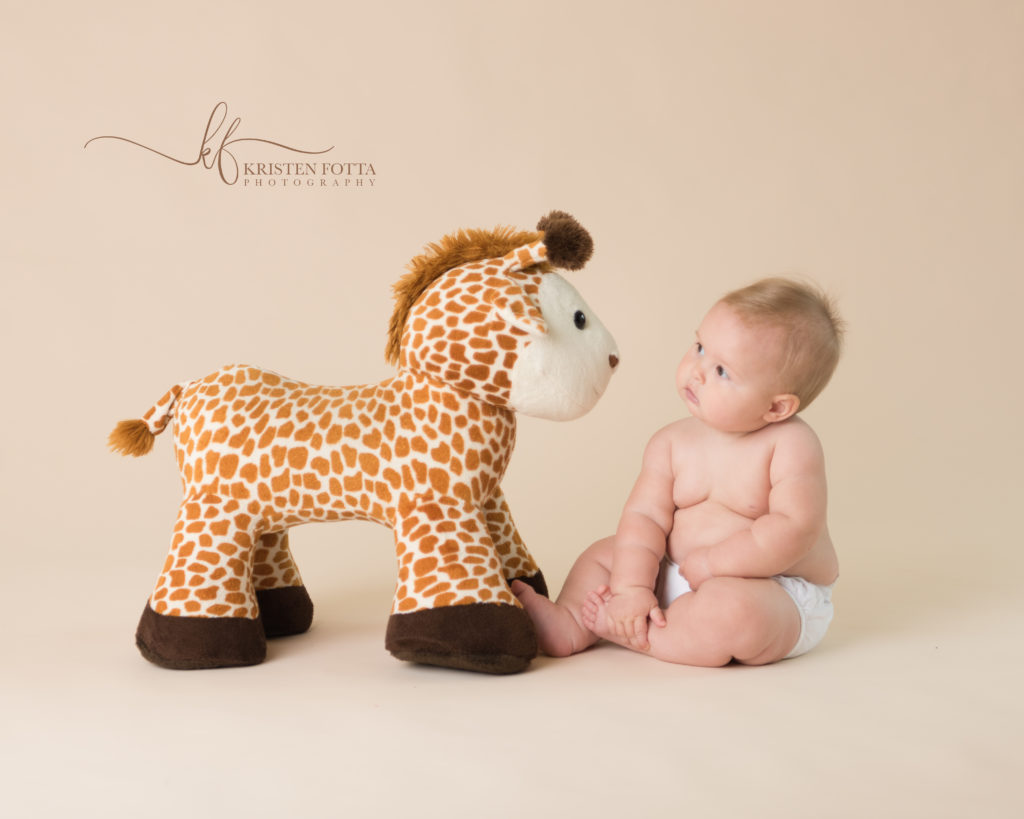 6 month old baby girl looking at stuffed giraffe