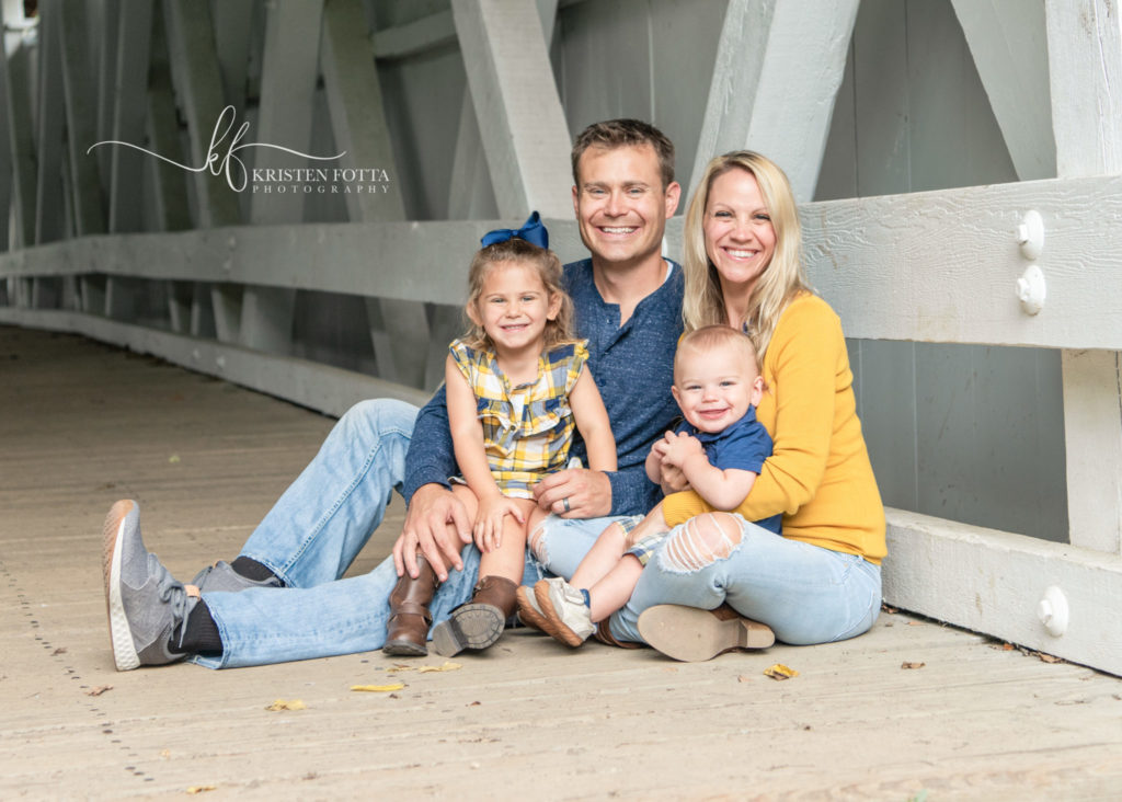 family dressed in blue and yellow sitting in covered bridge