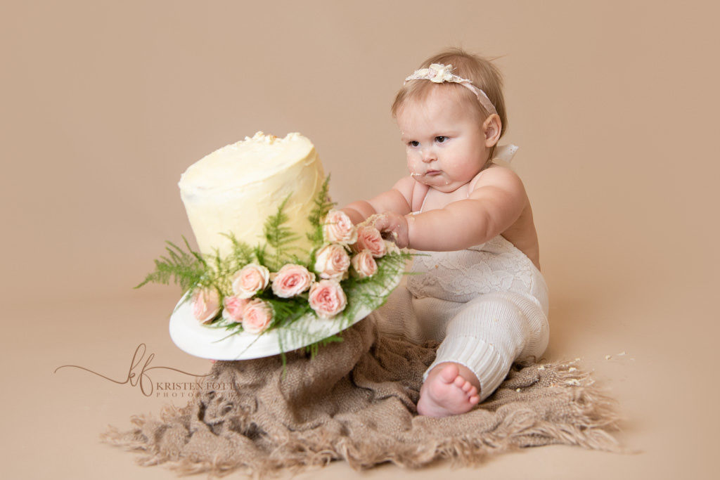 baby girl pushing her smash cake over