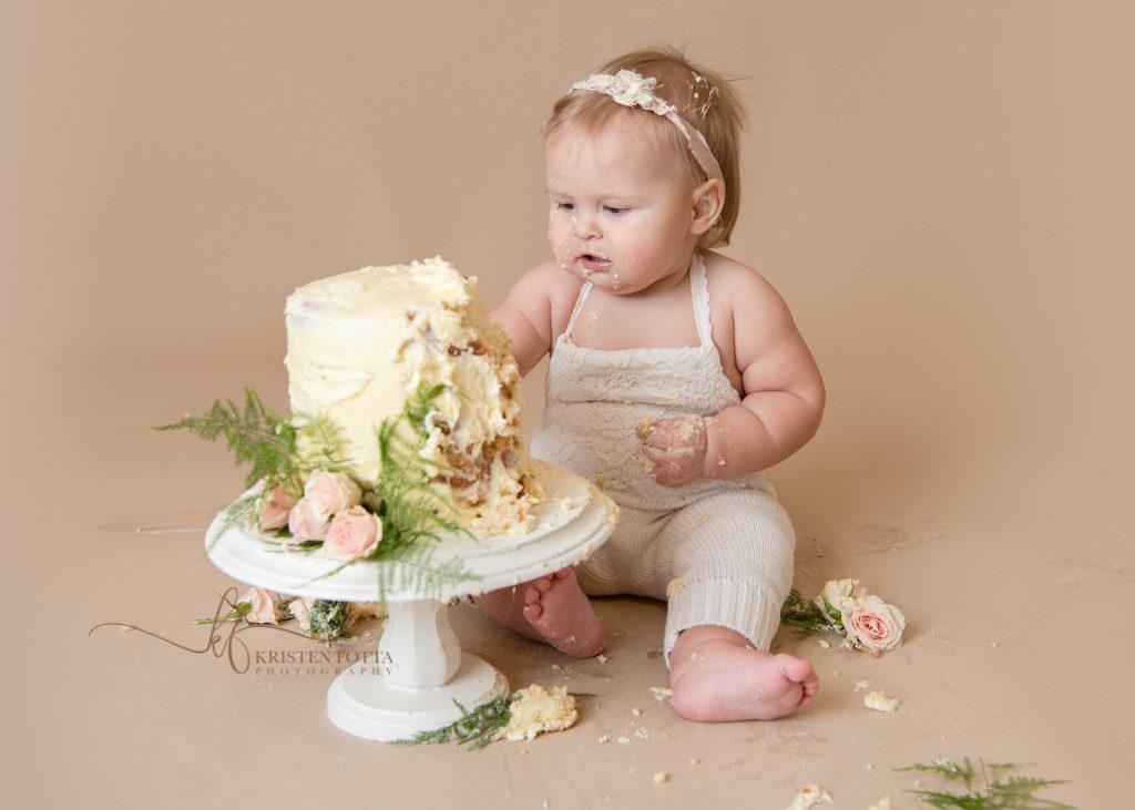 baby girl playing with smash cake