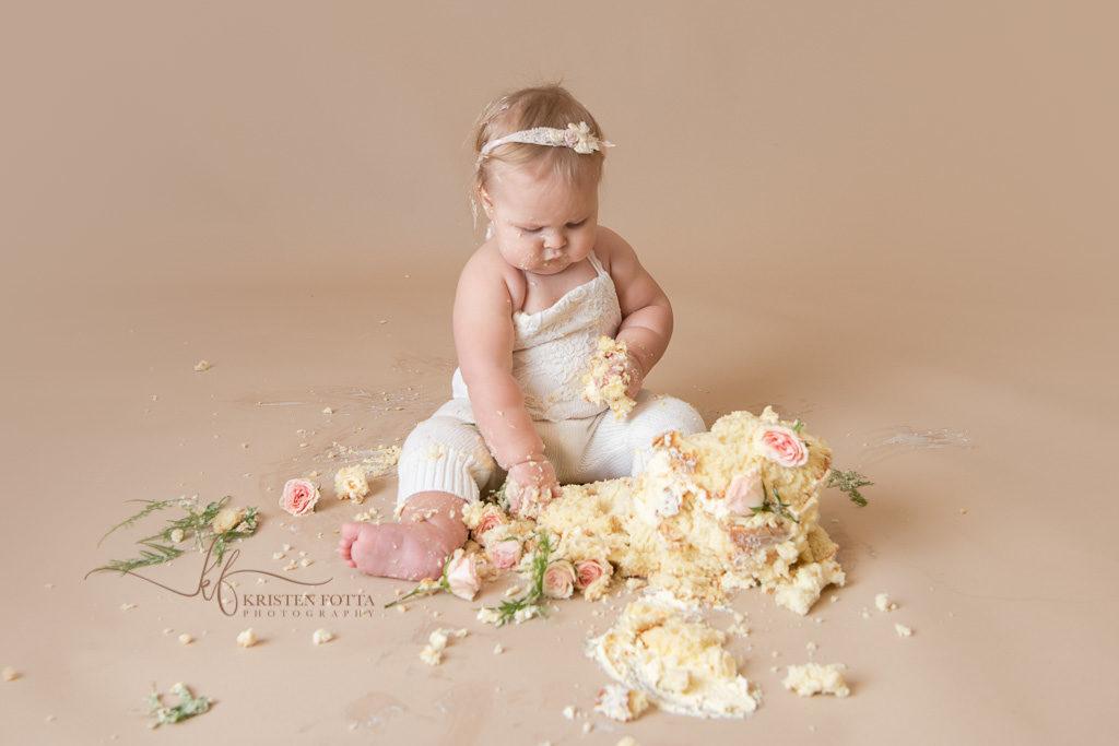 baby girl and first birthday smash cake