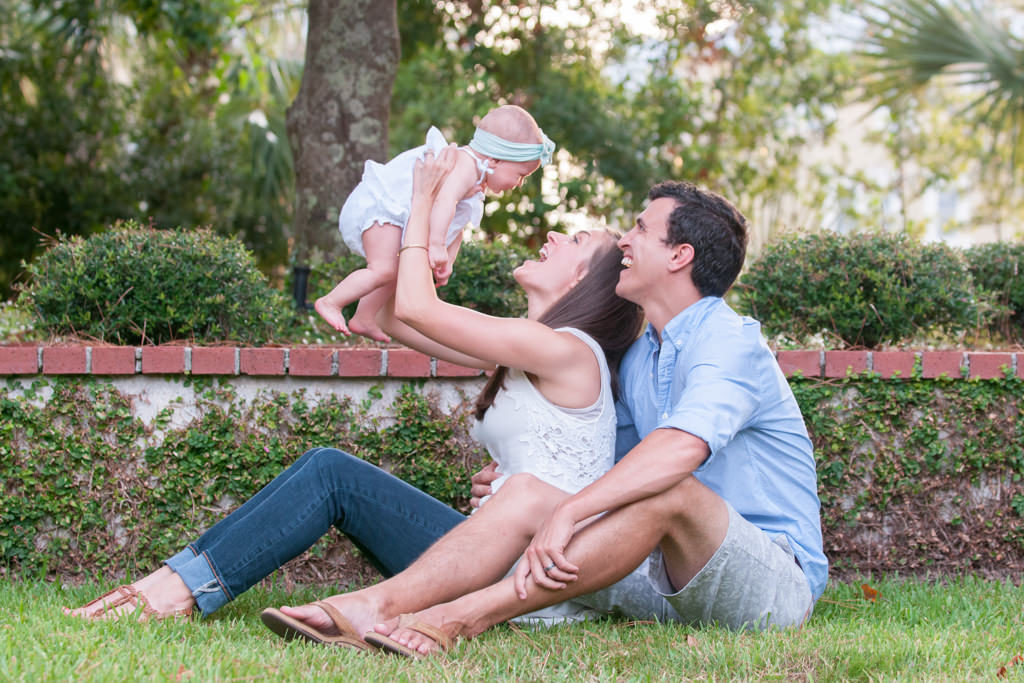 baby girl laughing as mom and dad fly her overhead at a family photo session