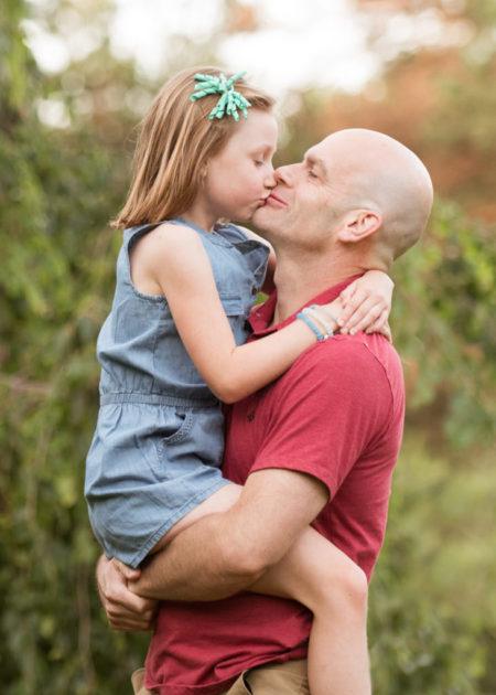 daughter kissing dad