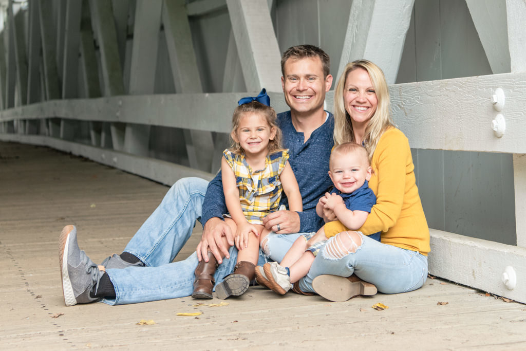 family picture sitting in covered bridge