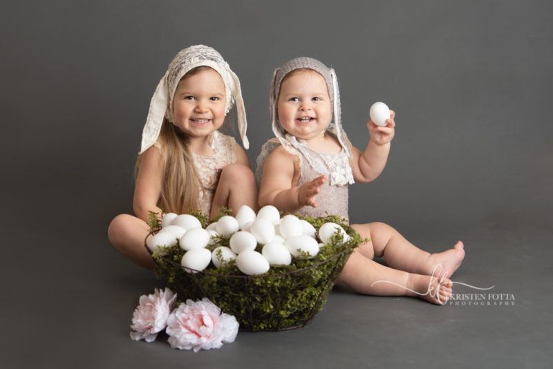 Studio Easter pictures of toddler sisters dressed in lace rompers and bunny ear bonnets