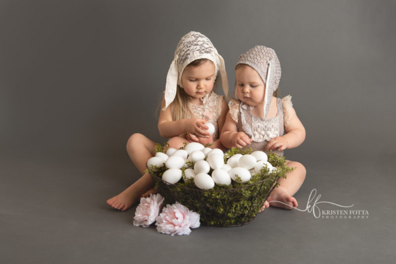 Studio Easter pictures of sister dressed in lace rompers and bunny ear bonnets