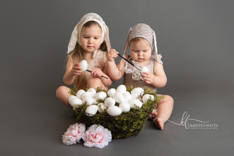 toddler girls wearing vintage inspired lace rompers and bunny ear bonnets painting a basket of Easter Eggs