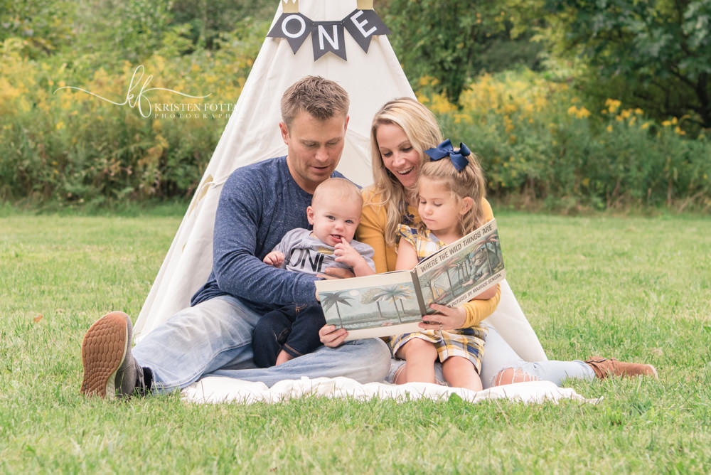 family reading a book together in a tent at a park