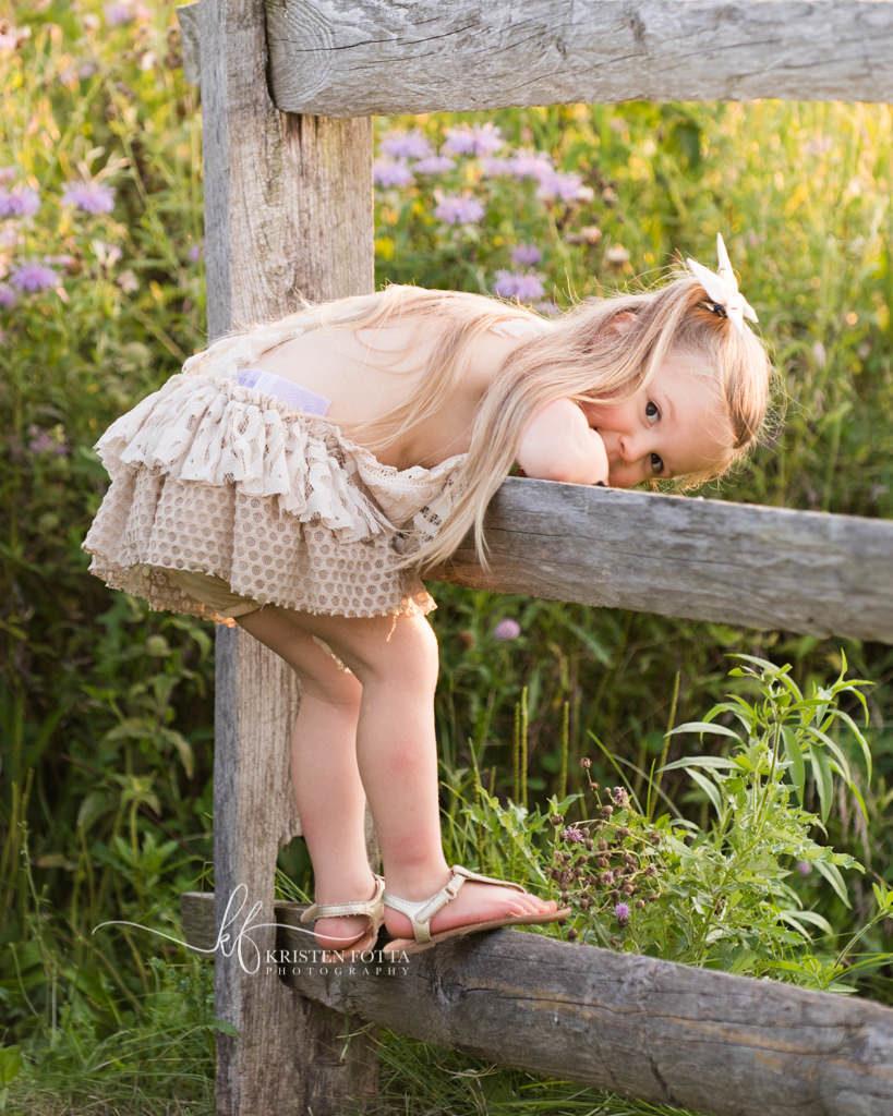 little girl by rustic fence in wild flower field
