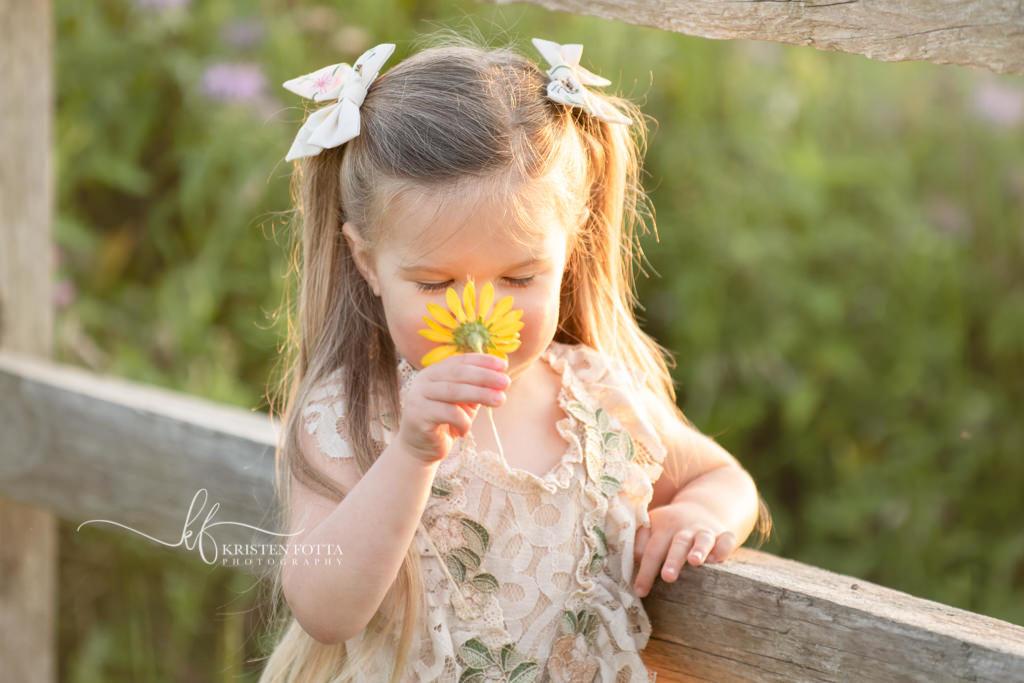 toddler girl smelling flower