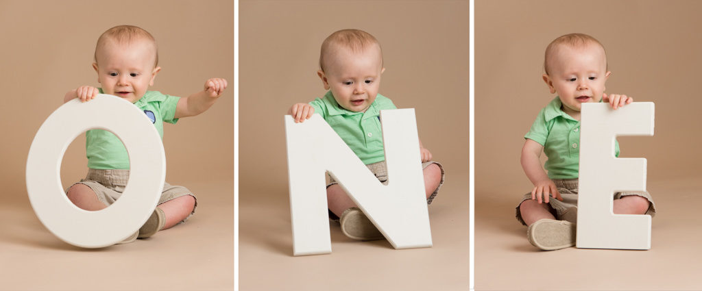 baby holding the letters O-N-E