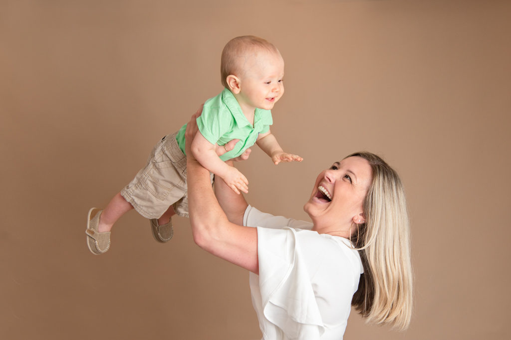 mom flying one year old baby in air during studio photography session