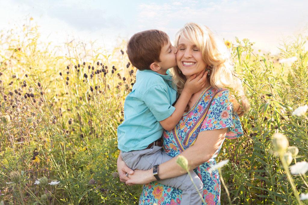 son kissing mom in wild flower field