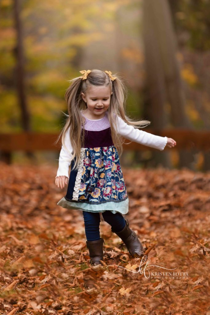 Toddler girl playing in fall leaves