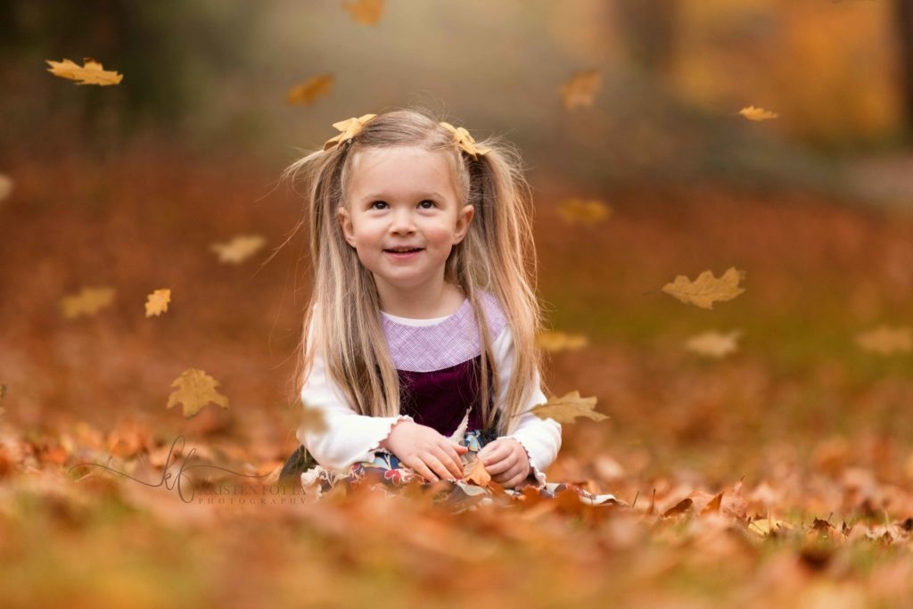 toddler girl watching fall leaves fall from overhead