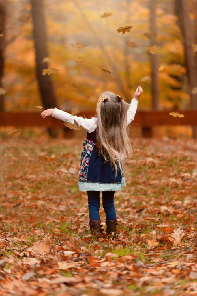 toddler girl throwing fall leaves into the air