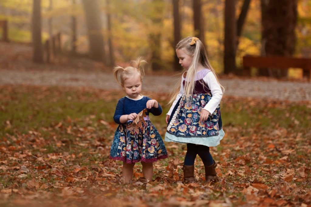 sisters looking at fall leaves outside