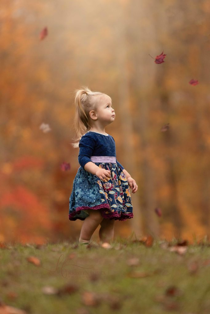 baby girl watching fall leaves fall to the ground