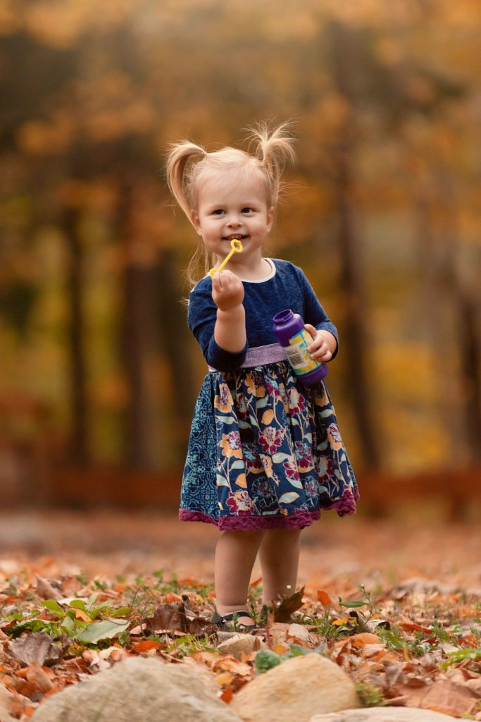 baby girl blowing bubbles outside in the fall leaves