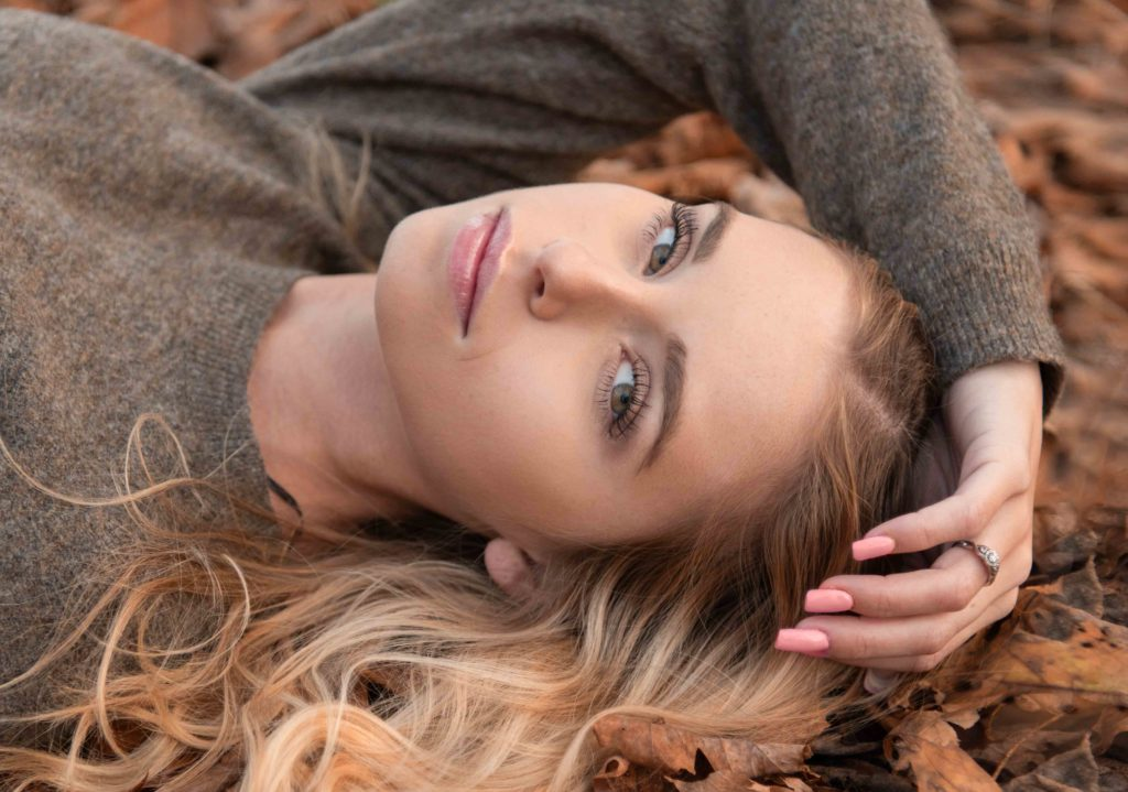 high school senior picture of girl laying in fall colored leaves