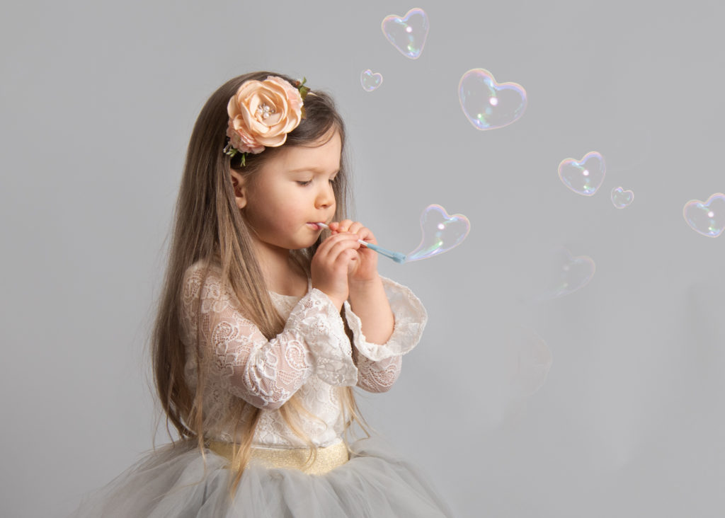 toddler girl blowing heart shaped bubble for Valentine pictures