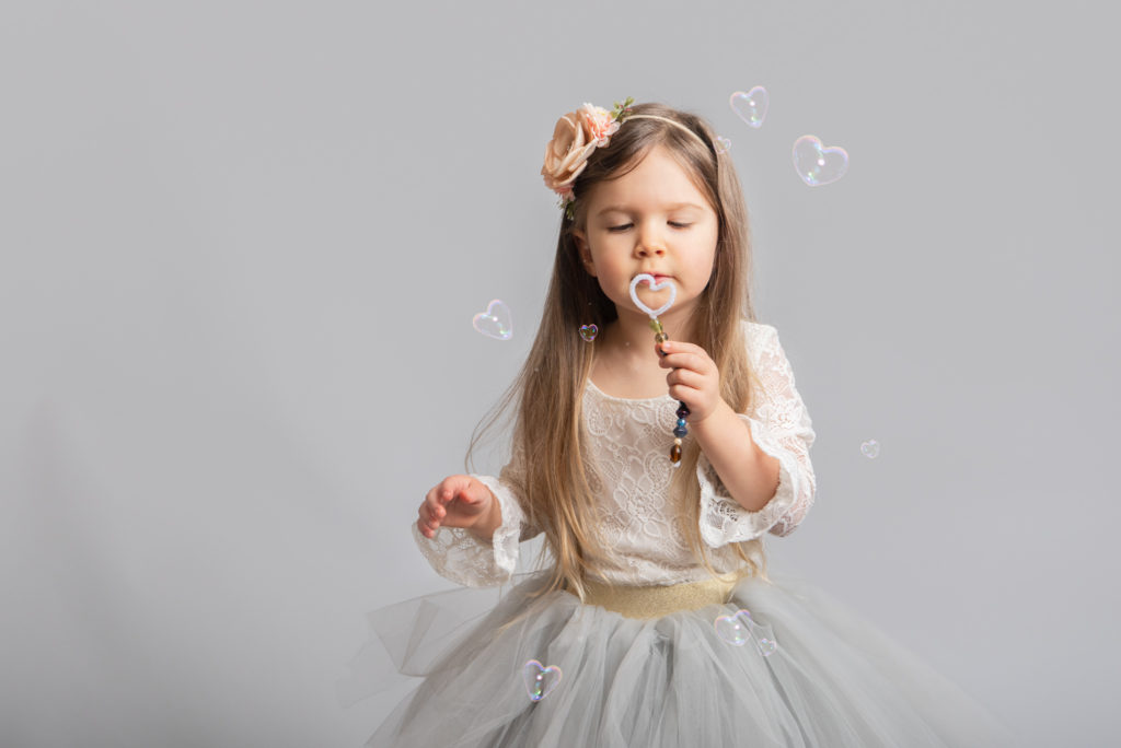 Toddler girl blowing heart shaped bubble for Valentine photo session