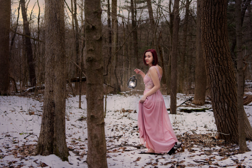 A girl in a ball gown walks the snow covered forest at night